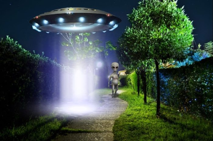 An image of a low-hovering UFO with a grey alien walking from it