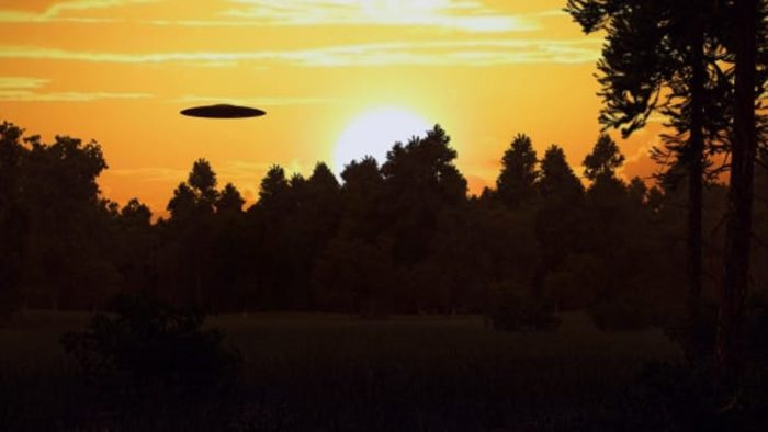 a depiction of a saucer shaped UFO over woodland at sunset