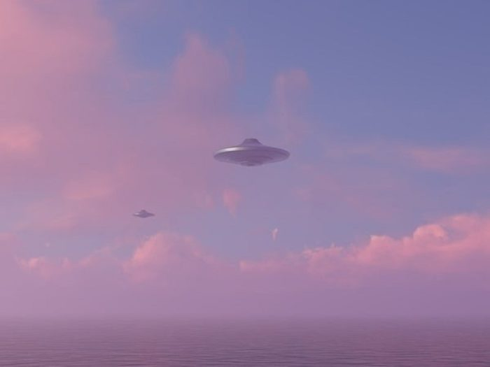 An image showing two UFOs hovering in the sky at sunset