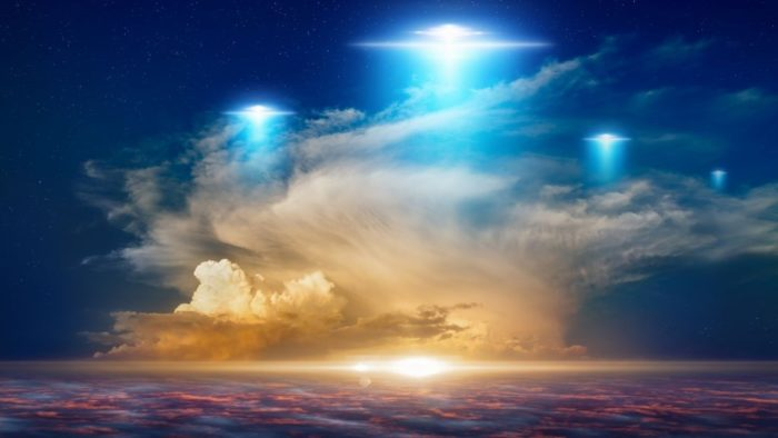 An image showing three glowing UFOs in a rich blue sky