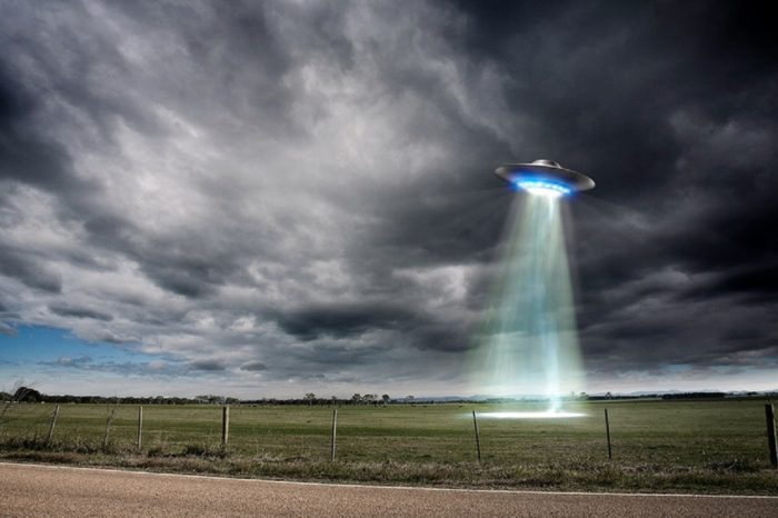 An image of a UFO hovering over a field