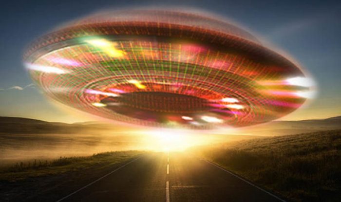 A depiction of a glowing UFO over a lonely highway at sunset