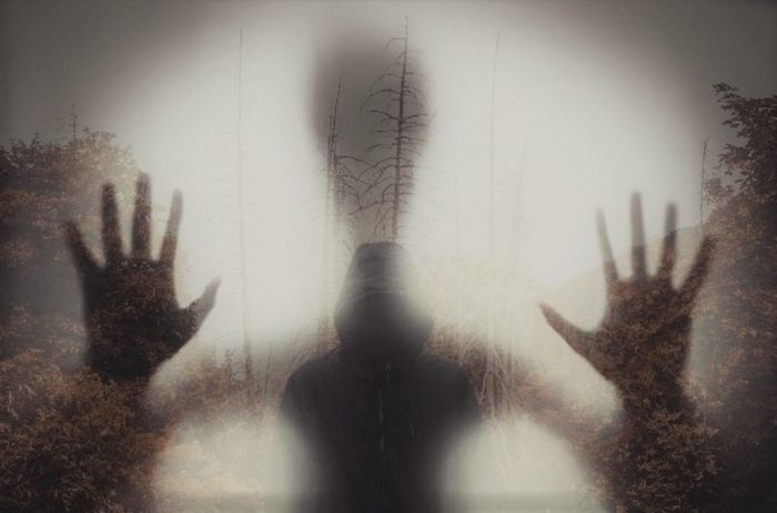 An image of hands pressed against the screen with a misty background