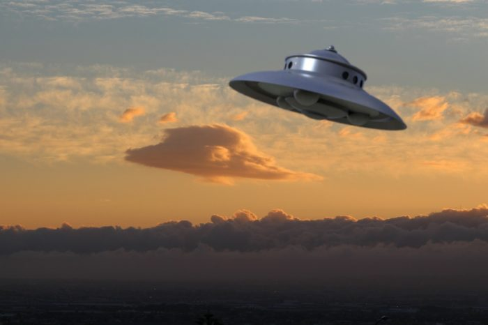An image of a UFO in a cloudy sky at sunset