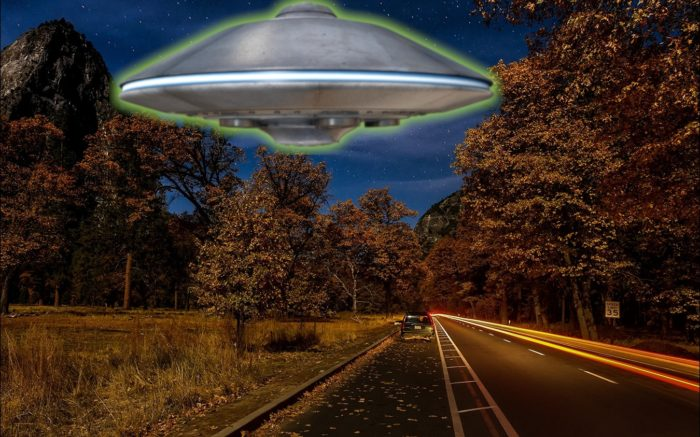 A superimposed UFO on a picture of a lonely road at night