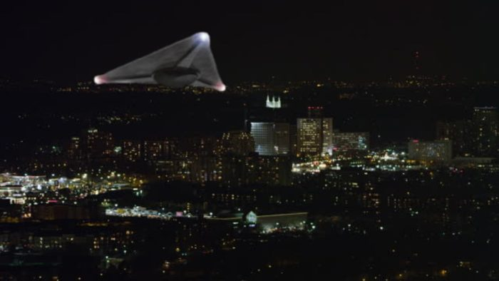 A superimposed triangular craft over a night city background