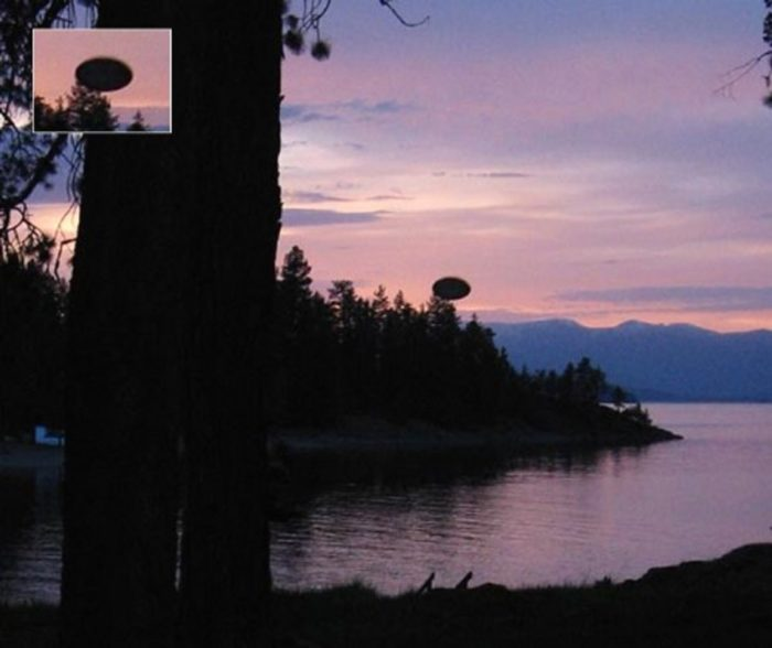 A picture showing an alleged UFO over a lake at sunset