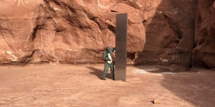 A person stood next to the Utah Monolith