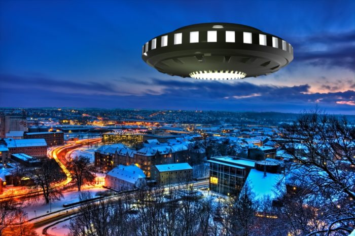 A superimposed UFO over a night scene of a snowy town