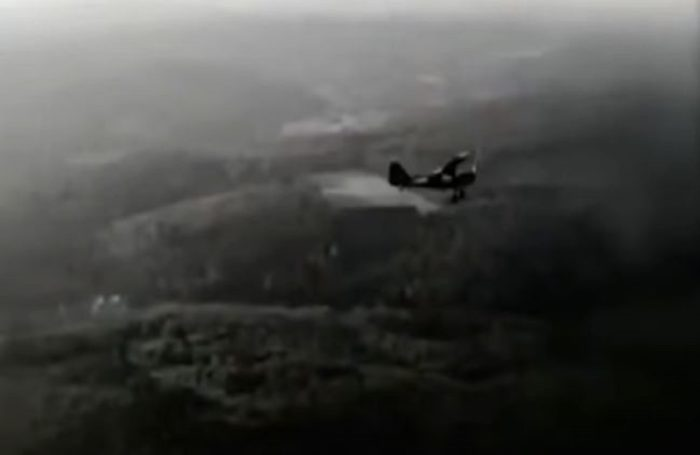 A picture of single engine plane flying over the countryside