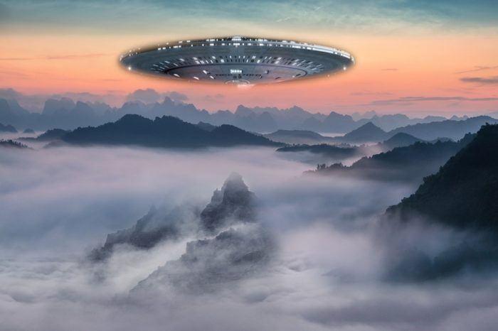 A UFO superimposed on a picture of a cloudy mountaintop