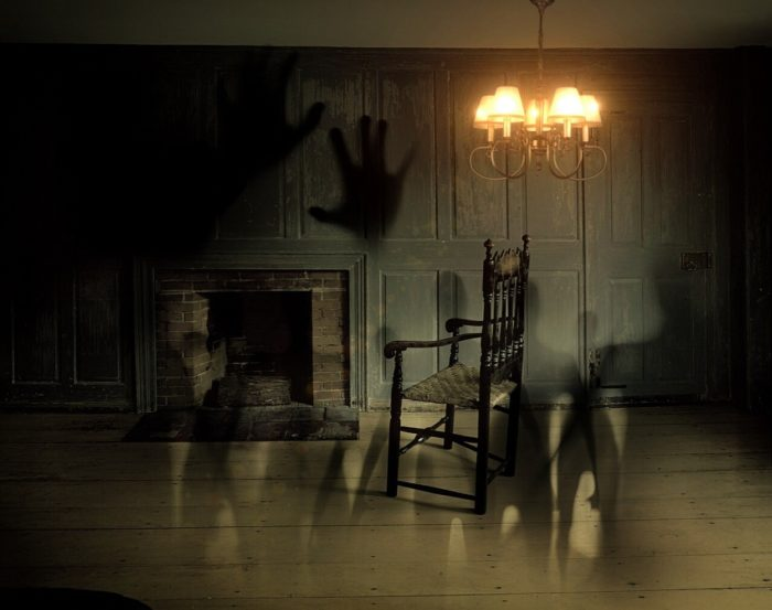 An old-fashioned room with ghostly hands and figures blended