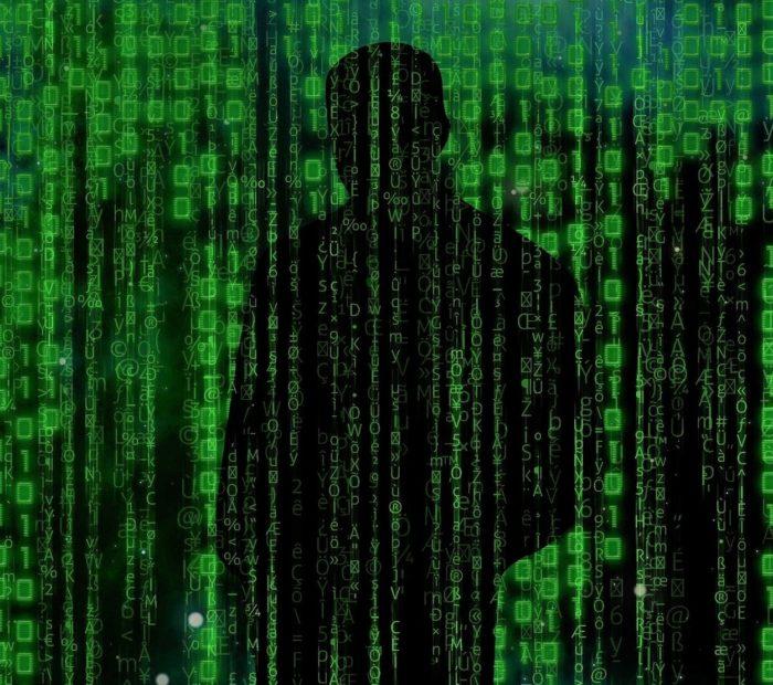 A black figure superimposed behind a digital computer screen