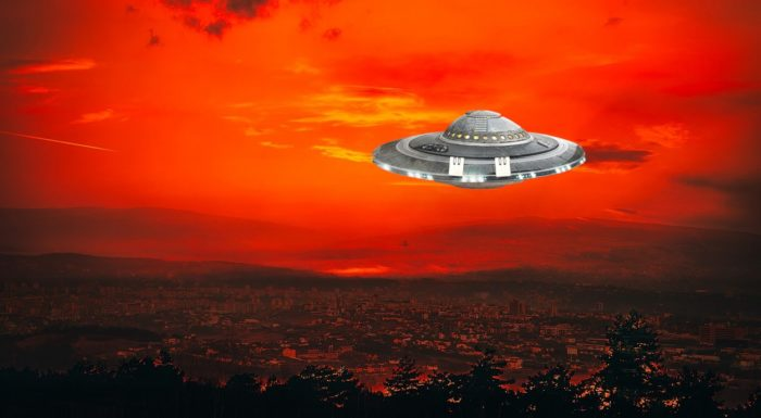An image of a UFO over a town at sunset