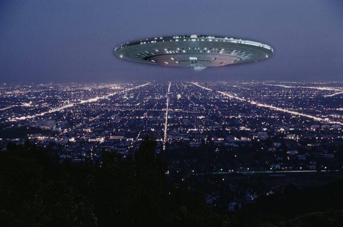 A superimposed UFO over an aerial shot of a city at night