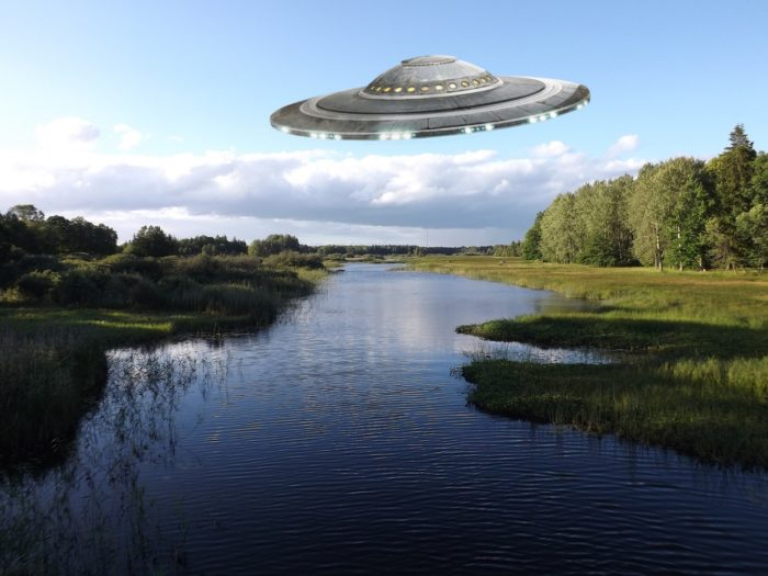 A superimposed UFO on a picture of a lake during the day