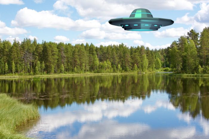 A superimposed UFO over a lake during the day