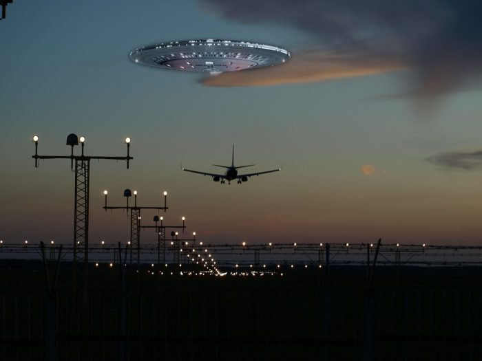 A picture of a plane flying into the distance with a superimposed UFO over the top