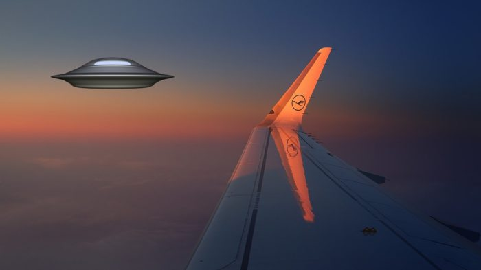 A picture of a plane's wing with a superimposed UFO at the side