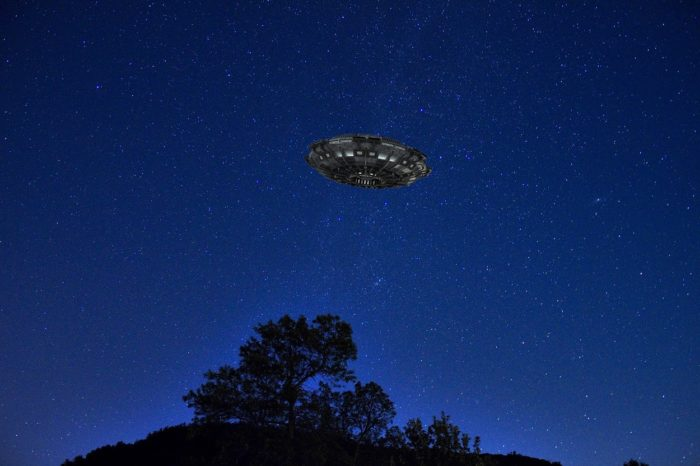 A superimposed UFO over a black tree at night