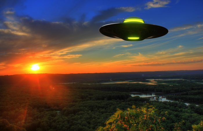 A superimposed UFO on a picture of the countryside at dawn
