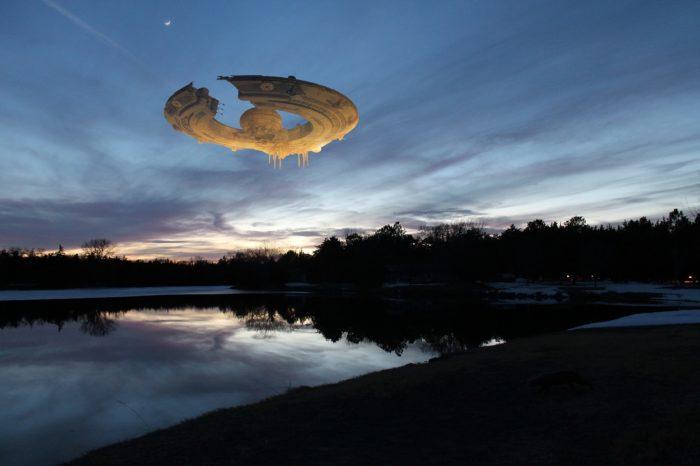 A superimposed UFO over a river at dawn