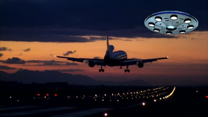 A superimposed UFO on a picture of a plane taking off from the runway at night