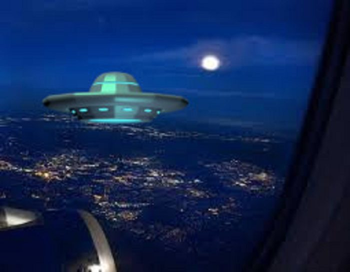A view of the land from the plane window with a superimposed UFO