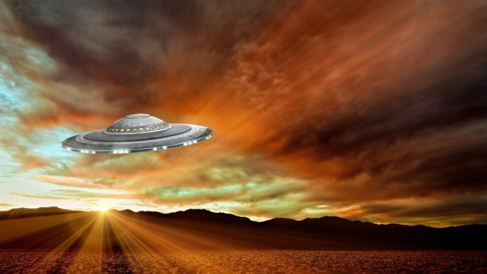 A superimposed UFO on a picture of a dawn sky