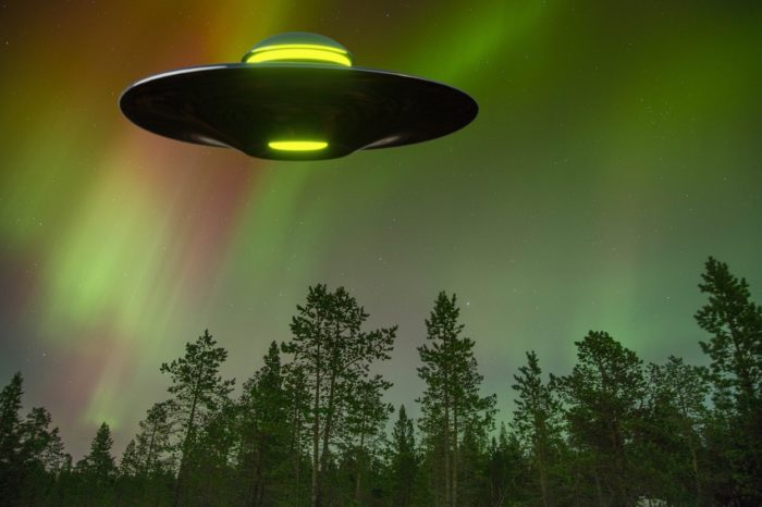 An image of a green glowing UFO over woodland at night
