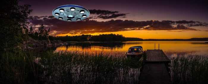 A superimposed UFO over a picture of a boating dock at sunset