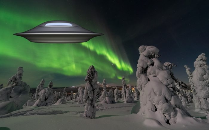 An image showing the aurora over snowy trees with a superimposed UFO over the top