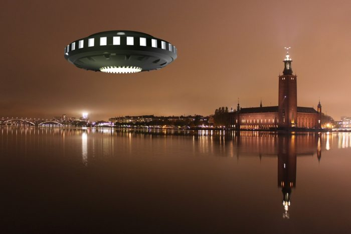 A superimposed UFO over a river with a glowing city in the background