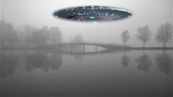 A superimposed UFO over a picture of a misty lake