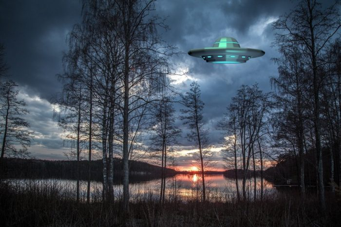 A superimposed UFO over a dawn image of a lake with trees