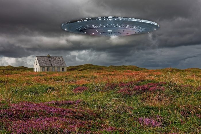 A superimposed UFO over an image of a lone house in a field with grey skies