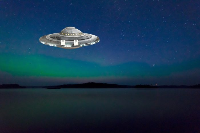 A superimposed UFO over a picture of a river at night