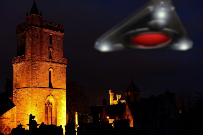 A superimposed triangular UFO over a picture of a church at night