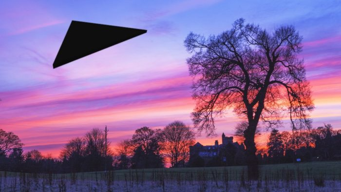 a superimposed black triangular UFO on a picture of the countryside at sunset