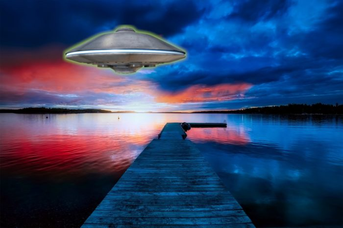 A picture of a UFO over a red and blue glowing lake