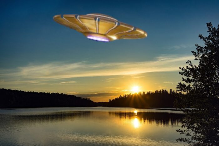 A superimposed UFO over a lake at dawn