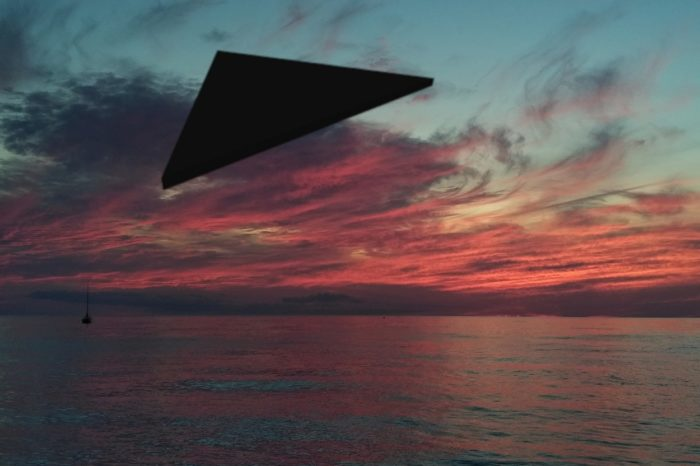 A superimposed black triangular UFO over water at sunset
