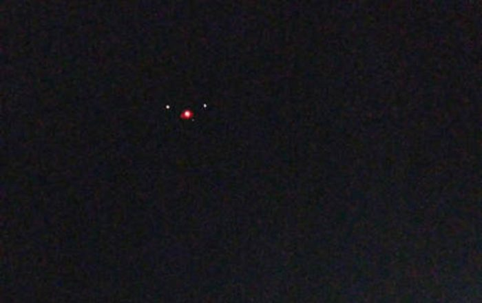 A picture showing an alleged triangular shaped UFO with lights at each corner