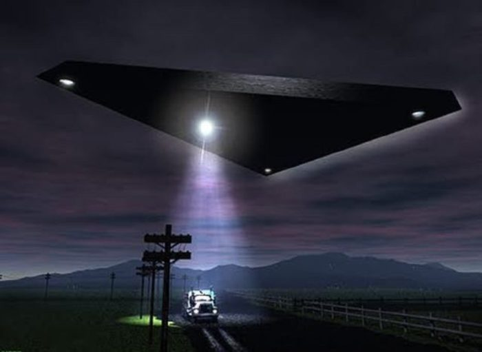 A depiction of a black triangular UFO hovering over a lone vehicle