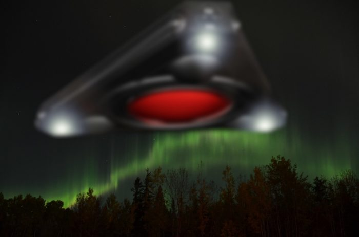 A superimposed triangular UFO over a forest with aurora sky