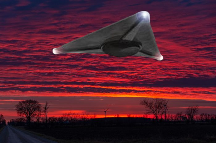 A superimposed triangular UFO with a red sunset sky behind