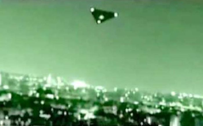 A picture showing a black triangle UFO at night over a city