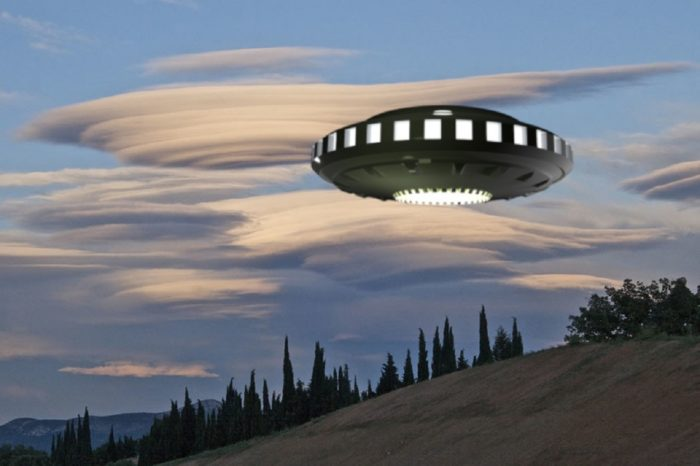 A picture of a UFO hovering over a woody hill