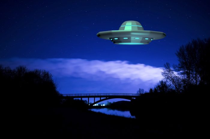 A picture of a UFO over a river at night