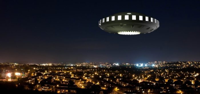 An image of a UFO over a picture of a city at night